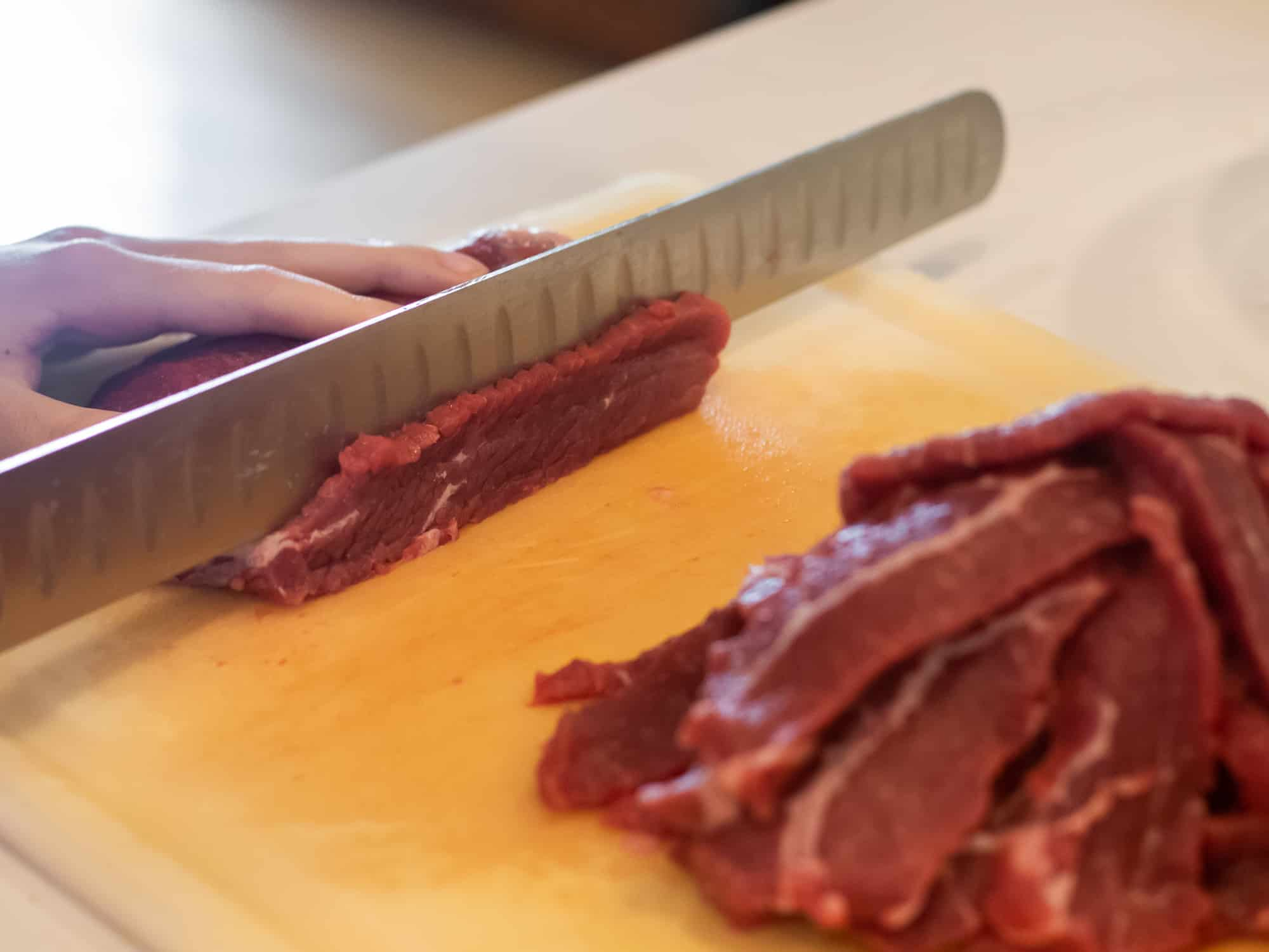 Slicing the beef round roast into thin strips.