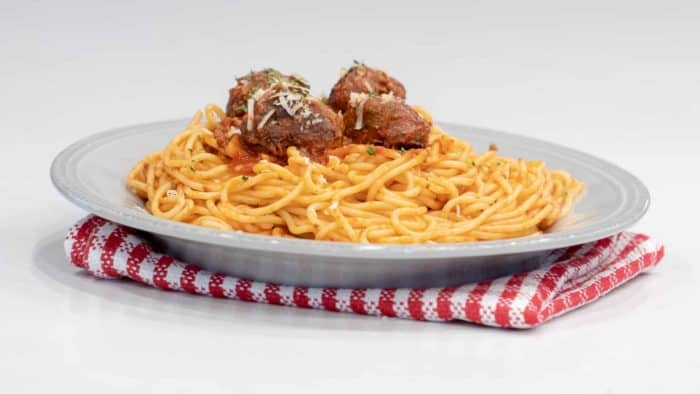 A plate of spaghetti topped with four meatballs and sauce.