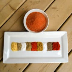 A plate with colourful spices piled next to each other.