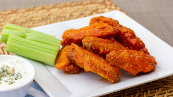 Restaurant style buffalo chicken wings made at home. Easy to prepare wings recipe with a traditional hot and spicy sauce using Frank's or other hot sauce. Great deep fried tail gate party snack.