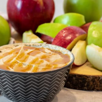 Bowl of creamy caramel dip with sliced apples