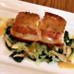 A pan seared filet of halibut served on a bed of sauteed leeks, spinach and oyster mushrooms drizzled with a honey mustard sauce.