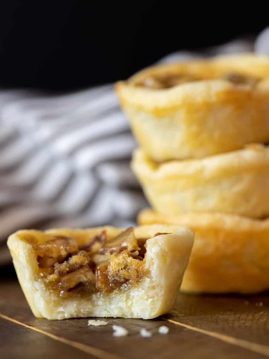 A tall close up image of mini butter tart desserts.