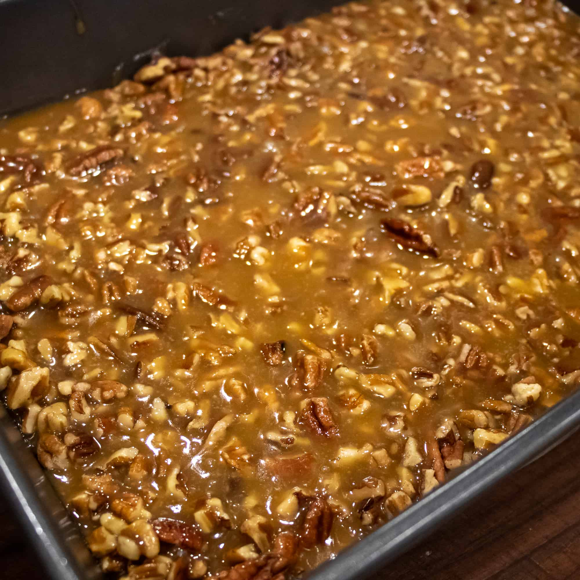 Pour the caramel and pecans over the crust layer.