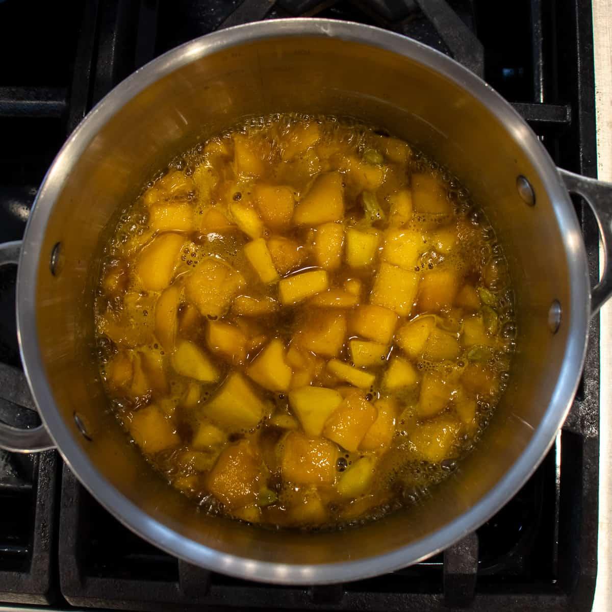 Diced mangos simmering in a saucepan.