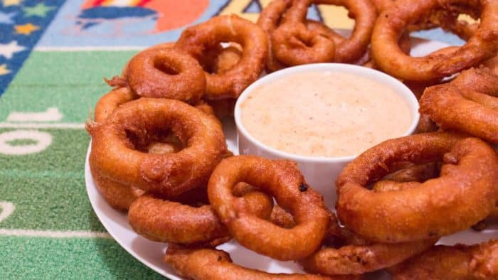 Light and crispy onion rings recipe that are deep fried in a beer batter coating with a cajun dip similar to the kind from Outback Steakhouses Bloomin' Onion.