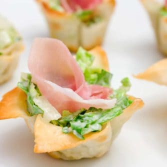 This wonton cup recipe is a snap to make and filled with caesar salad, parmesan cheese and a slice of prosciutto. They look amazing and taste delicious!