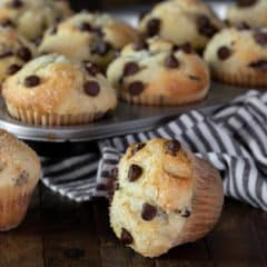 Muffin tray with chocolate chip muffins with a striped tea towel