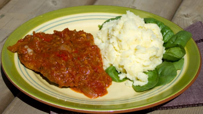 Swiss steak takes a cheap and tough cut of beef like round or sirloin steak (cube or minute), which is then braised in stewed tomatoes and other vegetables.