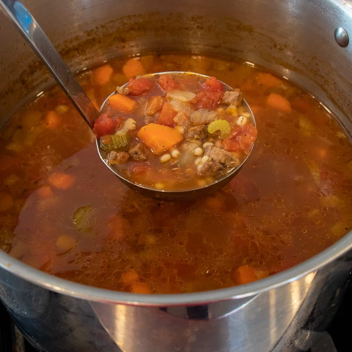 Scooping a ladle of fresh soup out of a large stock pot