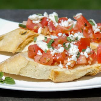 Recipe for how to make bruschetta bread with roma tomatoes, garlic, onion, lemon juice and olive oil. Topped with feta and oregano on a toasted slice of French baguette.