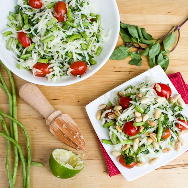 Thai green papaya salad recipe with grape tomatoes, peanuts, long green beans, thai basil, cilantro and a dressing made of lime juice, oil, fish sauce, sugar, thai chilies.