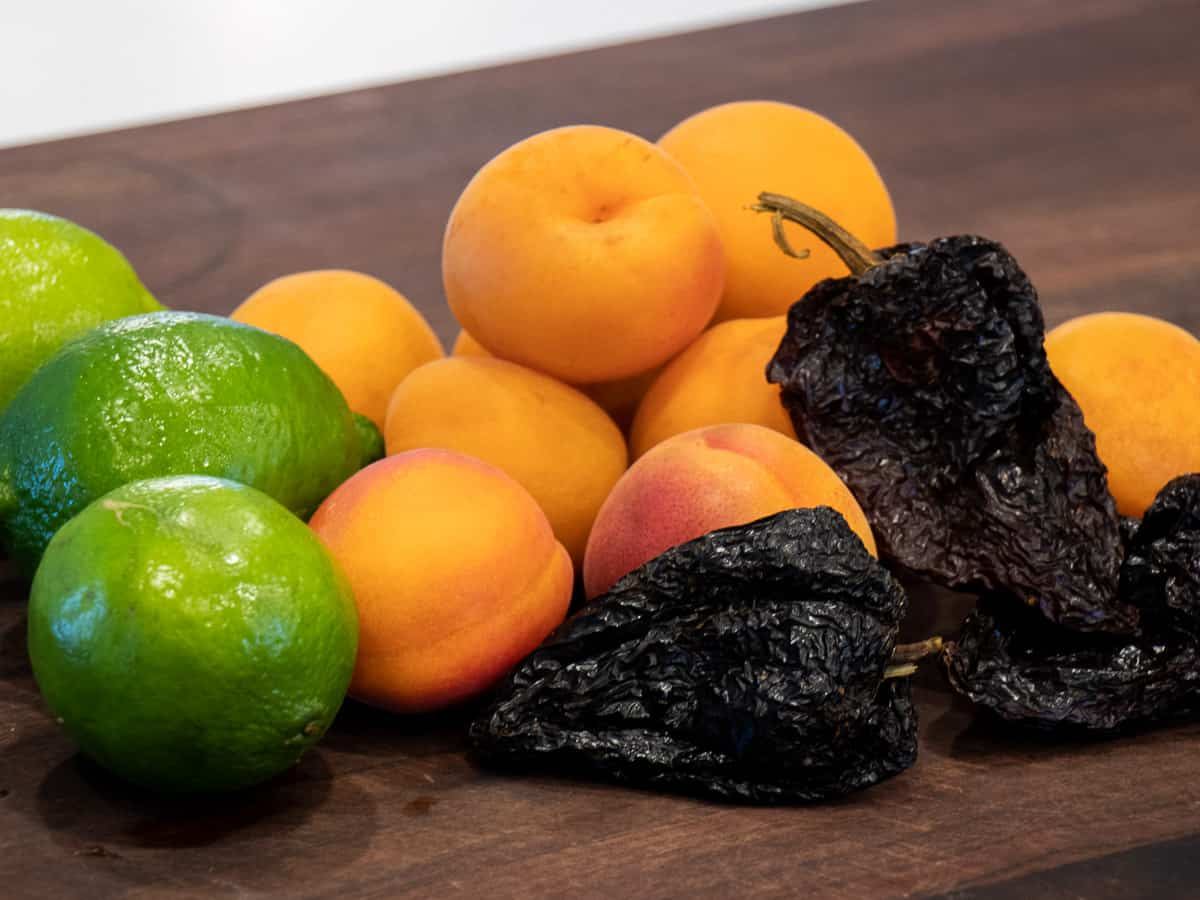 Fresh apricots, limes and dried ancho chilies.