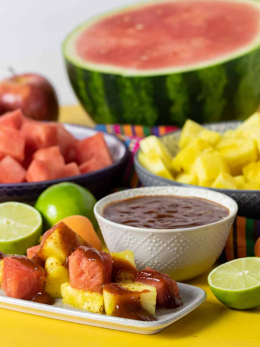 Plate of chopped watermelon and pineapple with bowl of chamoy sauce.