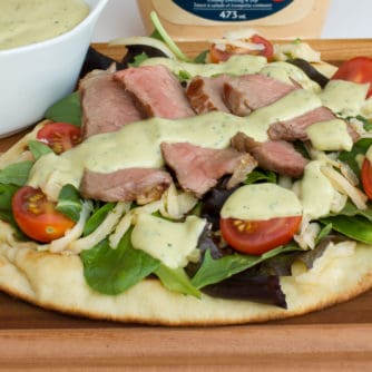 A grilled naan pizza with steak, grape tomatoes, mixed greens, pepper jack cheese and an avocado ranch dressing with cilantro, lime and hidden valley ranch spicy.
