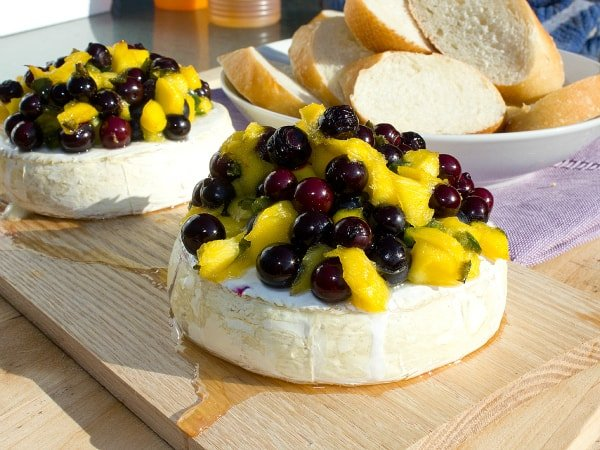 Easy recipe for how to plank grill brie cheese. Then topped with a fresh salsa of blueberries, mango, jalapeno, lime juice and a drizzle of honey.