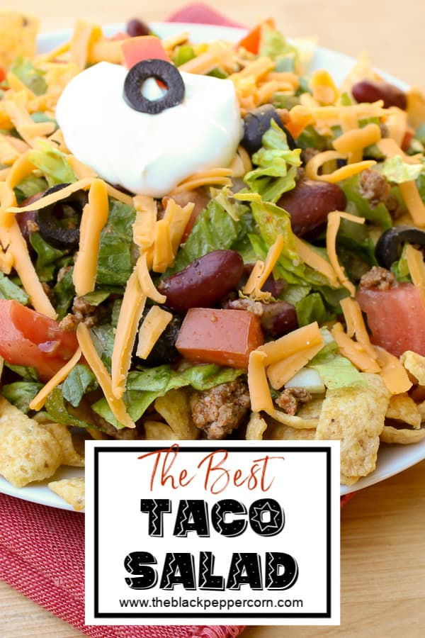 Taco salad recipe with romaine lettuce, ground beef, tomatoes, kidney beans, black olives, cheddar cheese, sour cream and Frito corn chips or nacho chips.