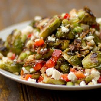 Roasted Brussels sprout salad recipe with bacon, walnuts, feta cheese, green onions, re peppers and a balsamic vinaigrette.