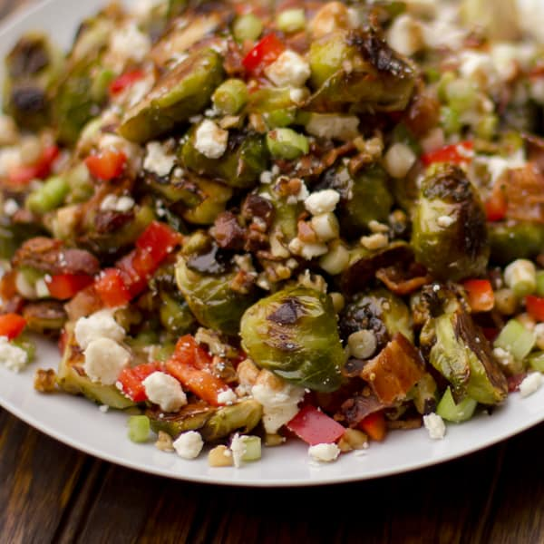 Roasted Brussels sprout salad recipe with bacon, walnuts, feta cheese, green onions, re peppers and a balsamic vinaigrette. Instructions for how to roast brussels sprouts.