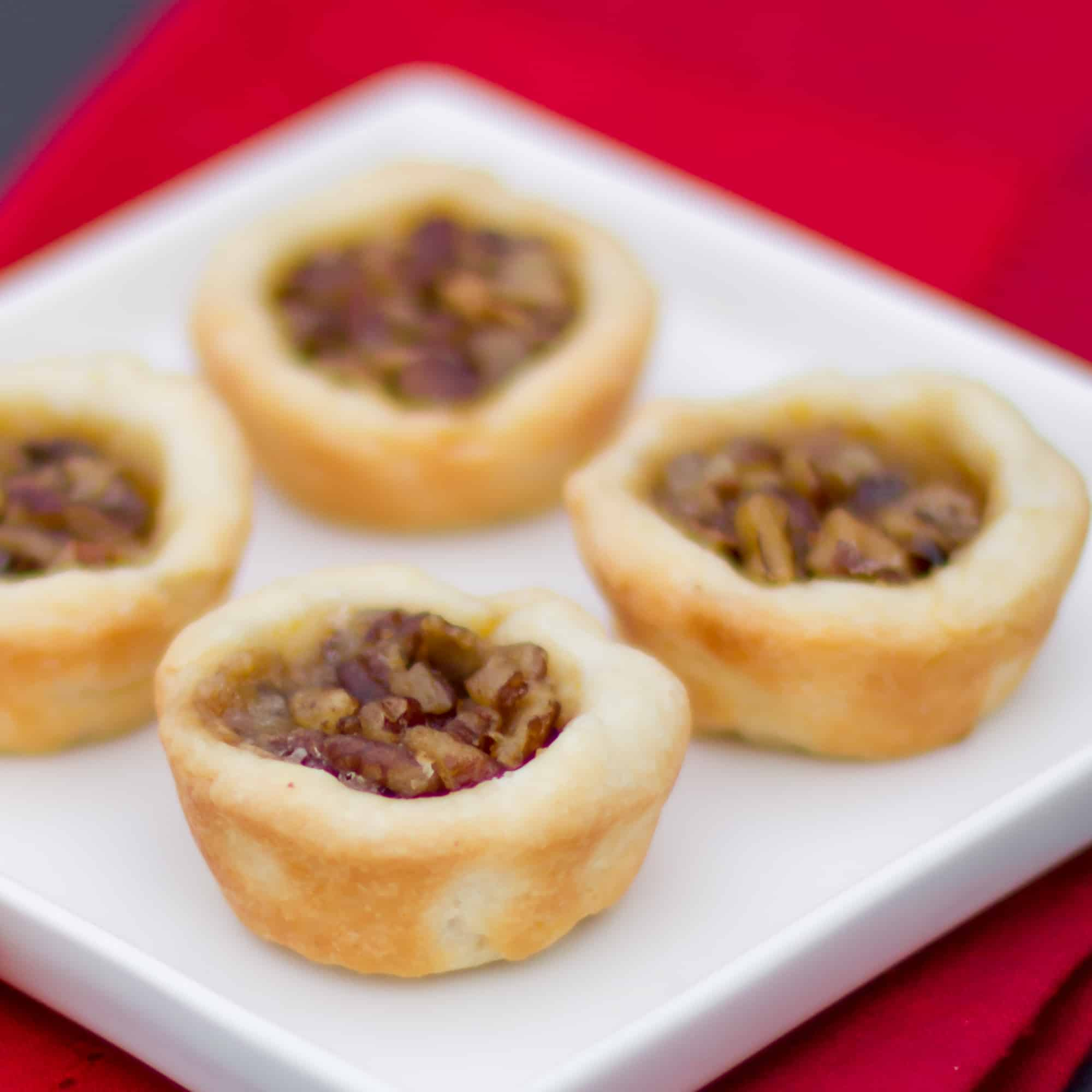 Maple syrup and pecans make up the filling in these mini tarts tassies that are simple and delicious. Cream cheese and butter pastry.