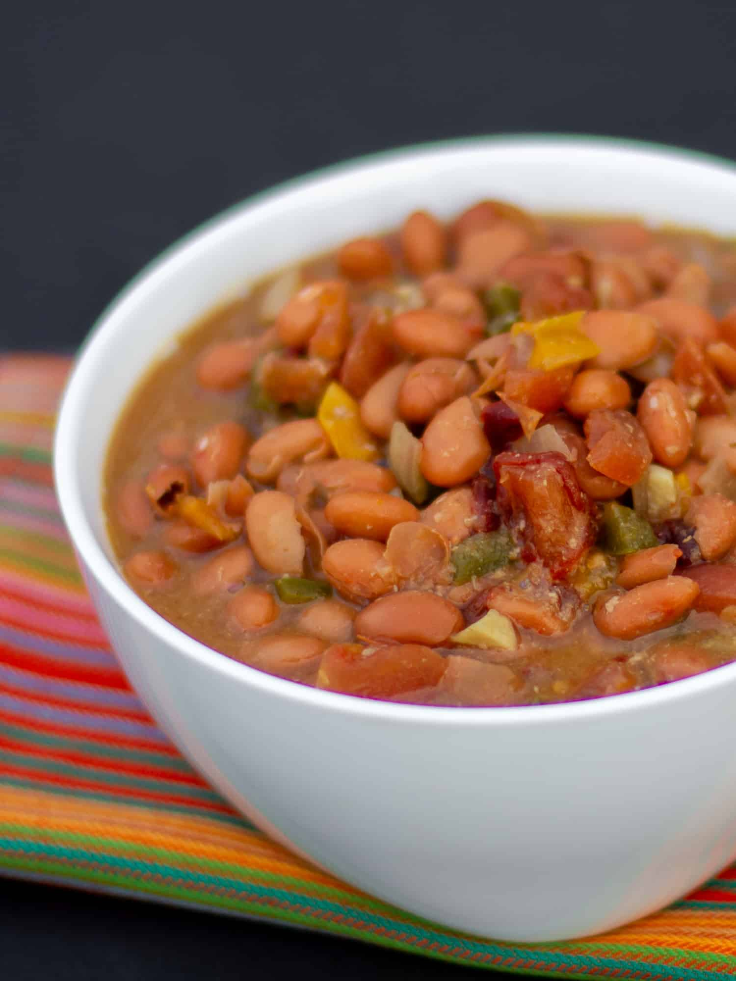 Slow cooked pinto beans with ham hock, tomato, onion, jalapeno and ancho chilies. Amazing tex-mex / Mexican comfort food baked bean recipe made in a Crock Pot.