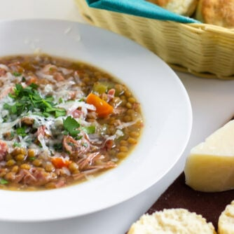 A warm bowl of soup with fresh baked biscuits.