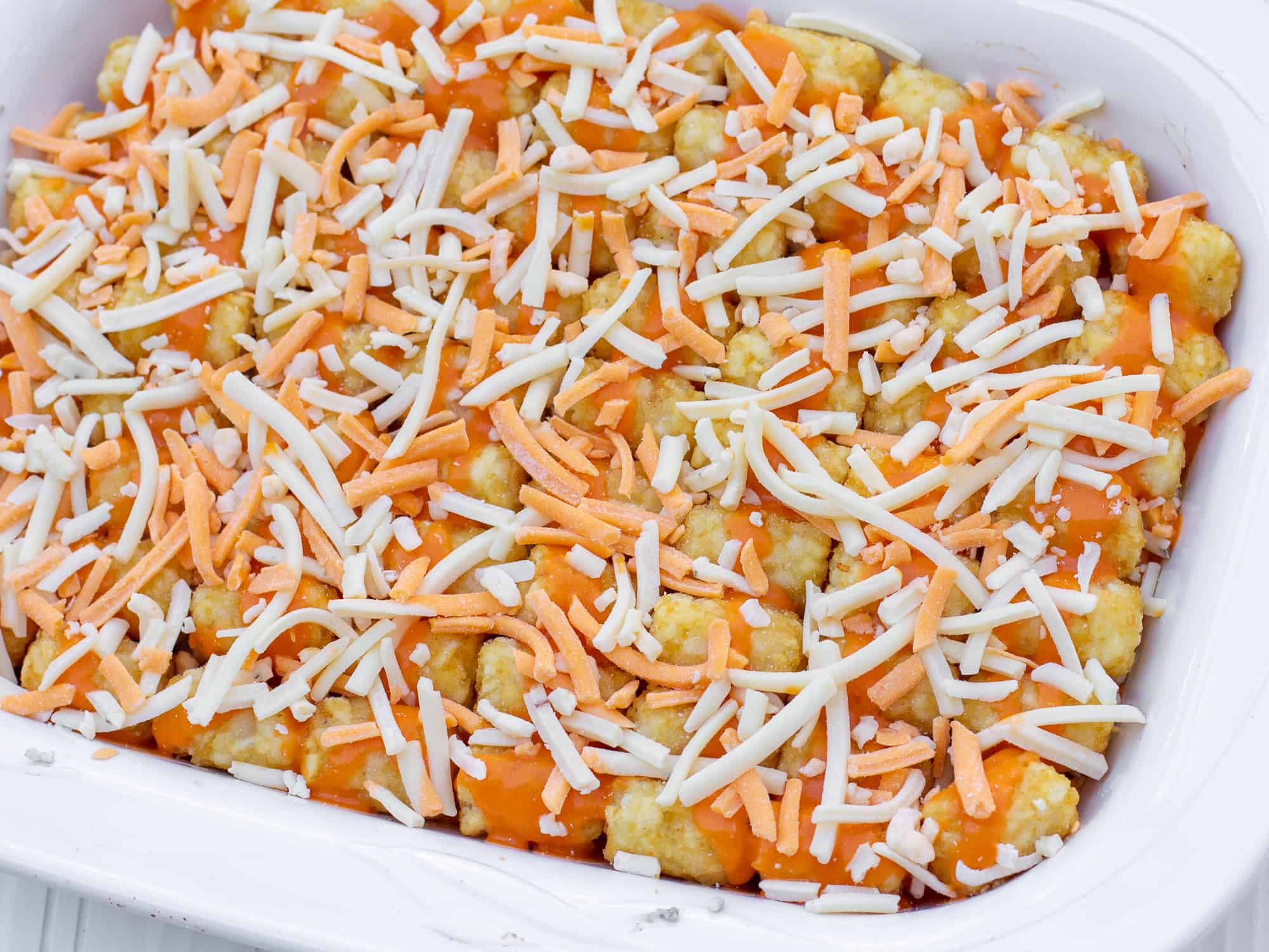 Place Tate Tots on top and drizzle with buffalo sauce and grated cheese