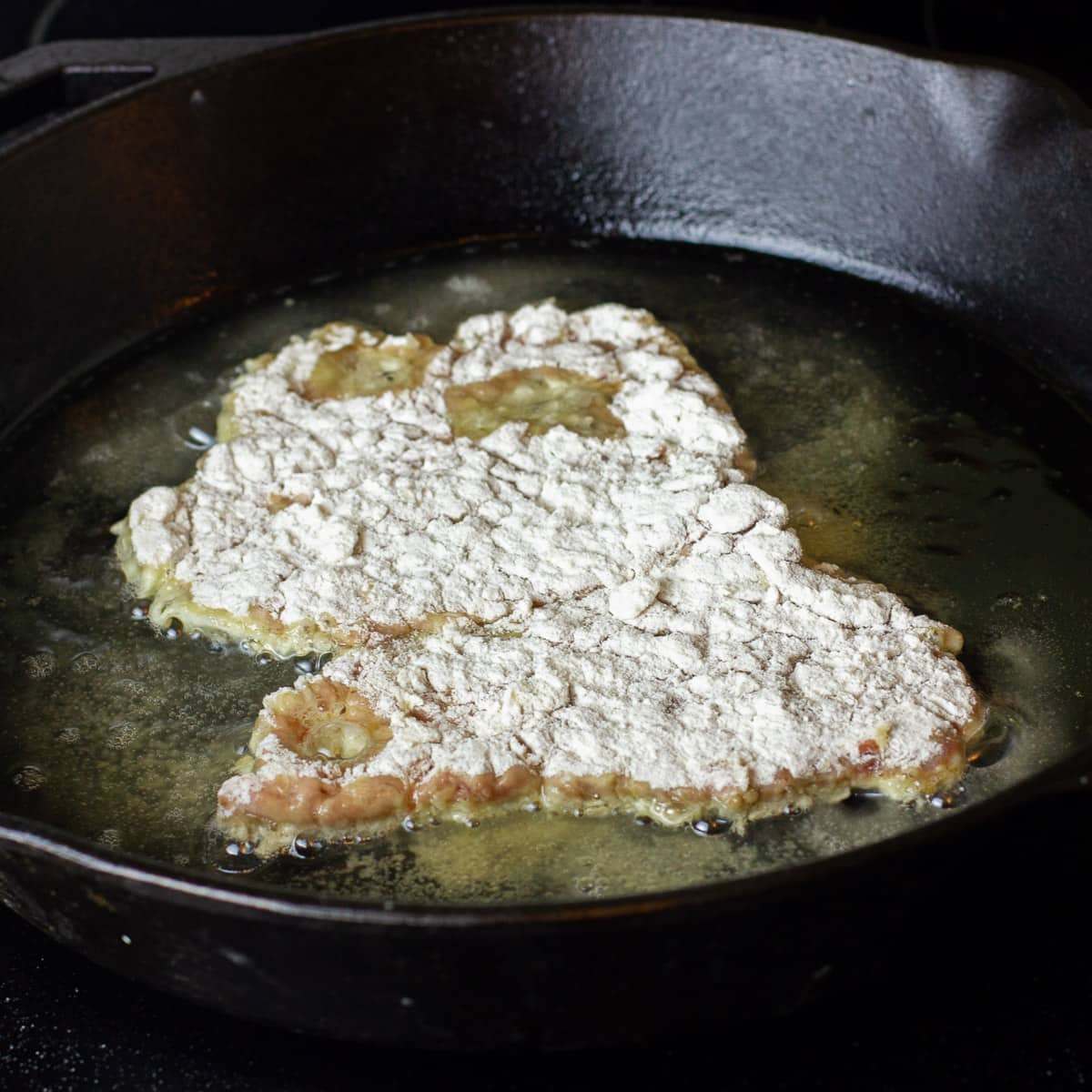 Dredge the tenderized steak with flour and egg wash.
