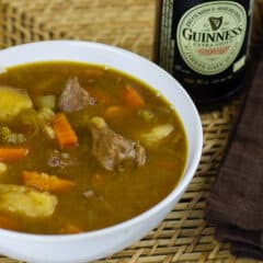 A overhead picture of a bowl of beef stew and a bottle of Guinness beer