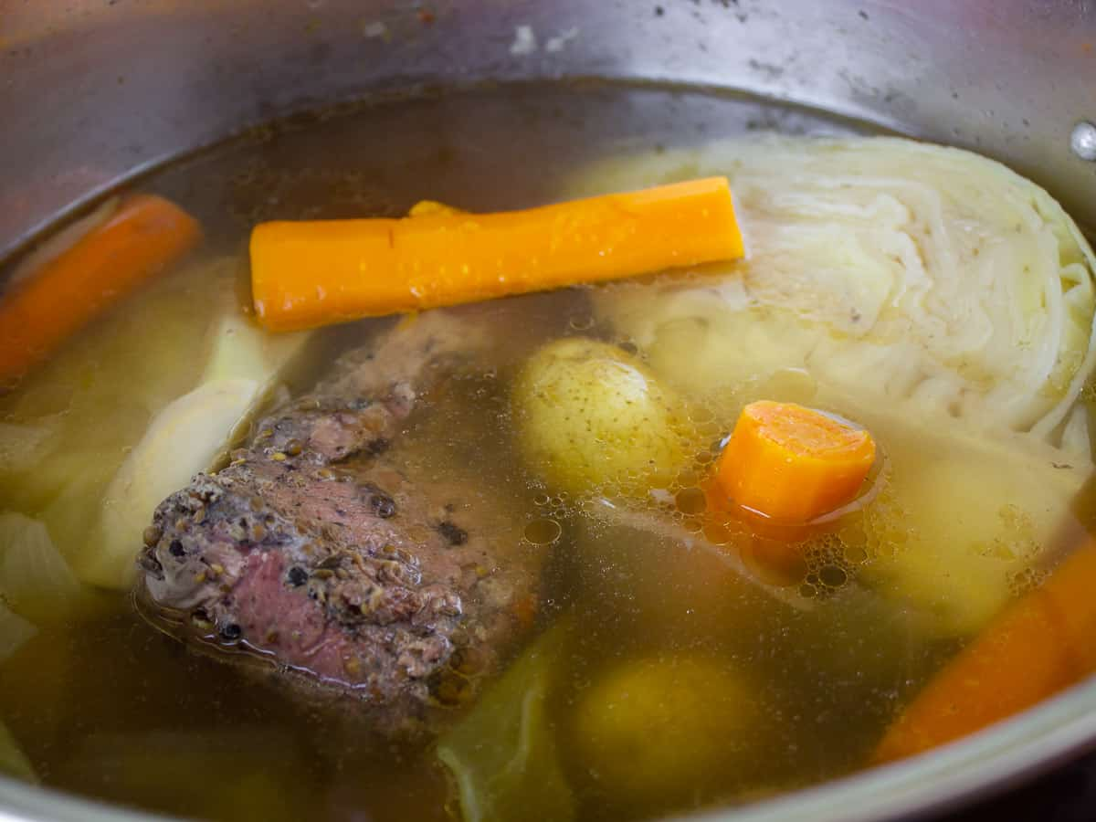 A pot willed with water corned beef, cabbage, potatoes and carrots.