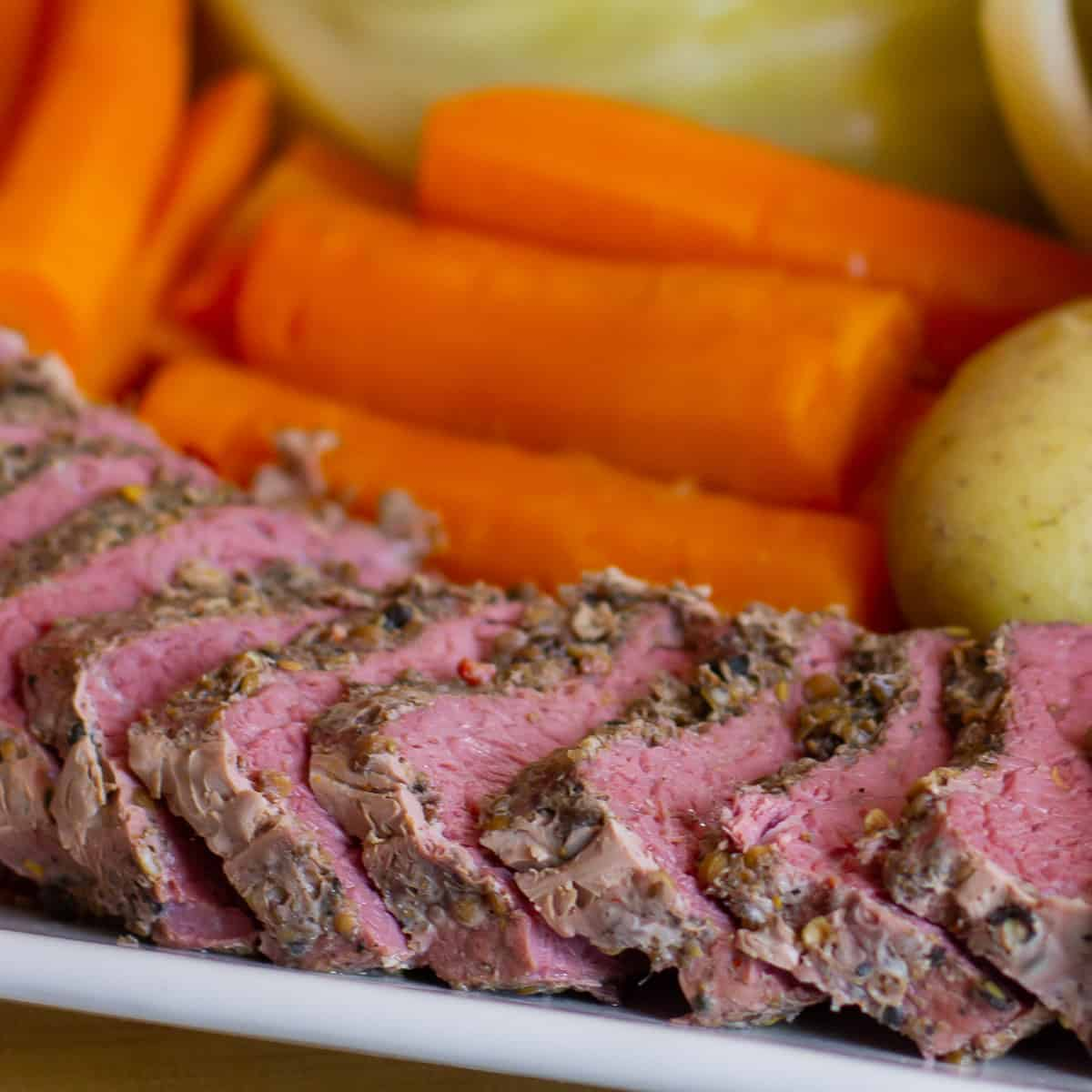Close up picture of sliced corned beef brisket and carrots