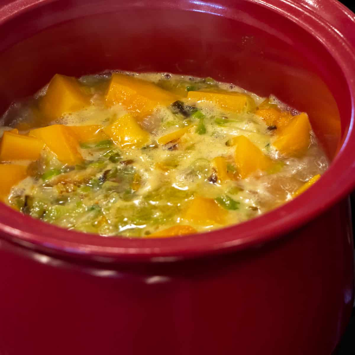 A pot with squash, leeks and onions simmering in a broth.