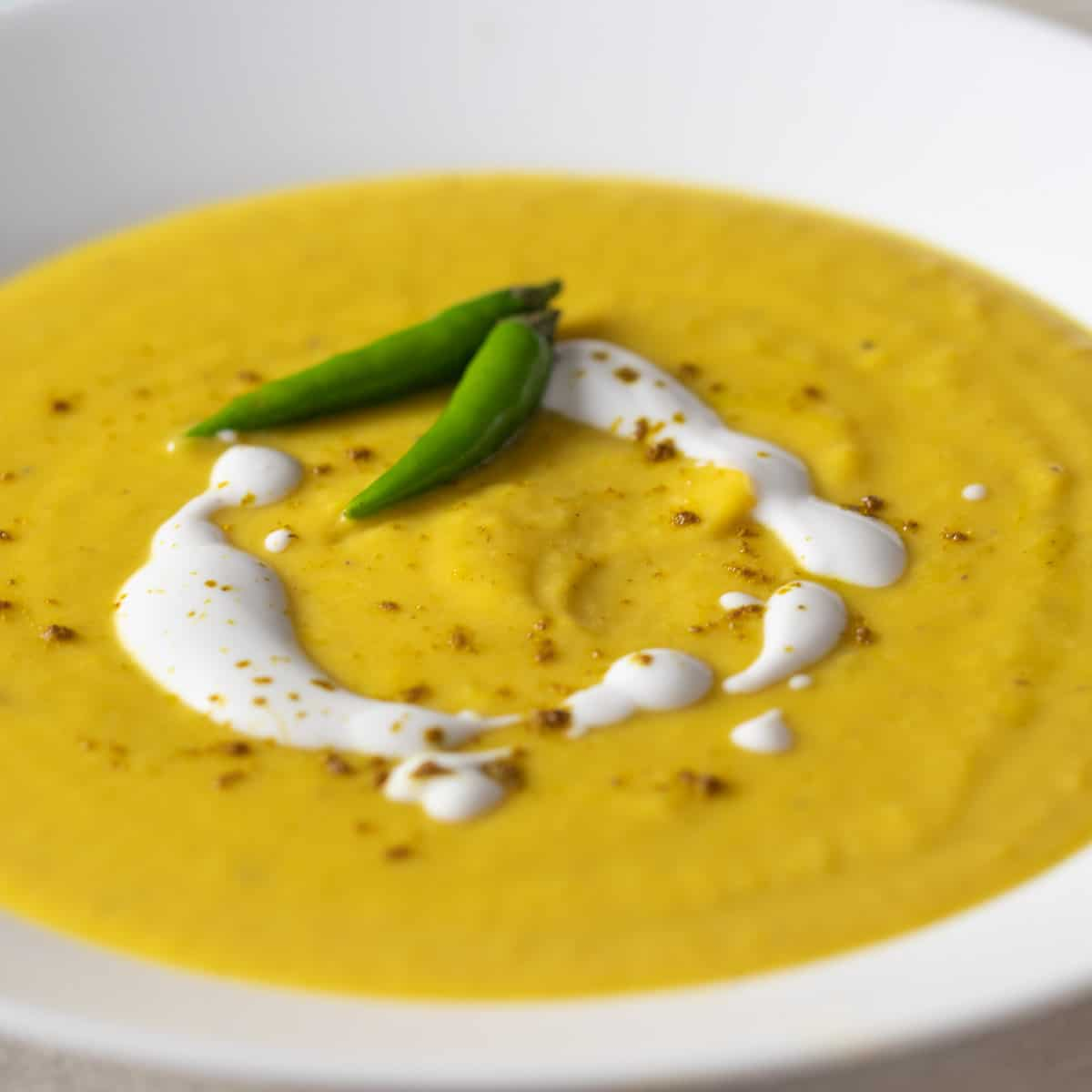 A closeup picture of a bowl of squash soup.
