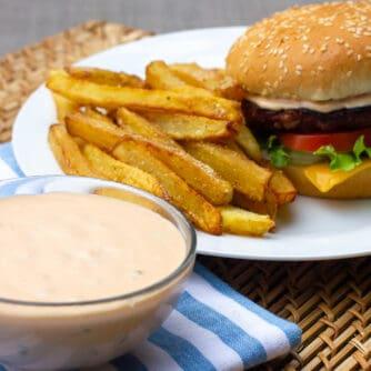 A bowl of Big Mac secret sauce with a burger and fries.