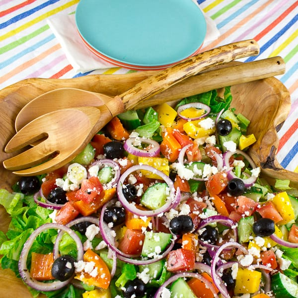 An overhead image of a large wooden bowl filled with Greek salad.