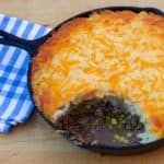 How to make shepherd's pie in a cast iron skillet! Baked recipe has beef filling with peas and corn, topped with mashed potatoes and grated cheddar cheese.
