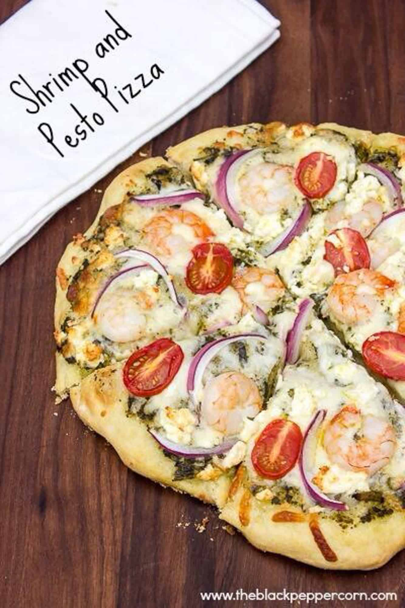 How to cook a pizza on a grill with this great BBQ pizza recipe, made with shrimp, pesto, red onions, grape tomatoes, feta cheese and mozzarella.