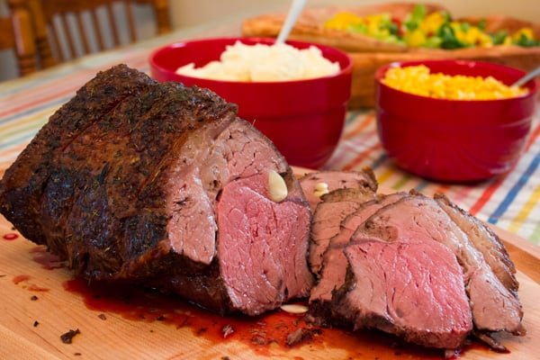 Cooked sirloin beef roast sliced on a cutting board