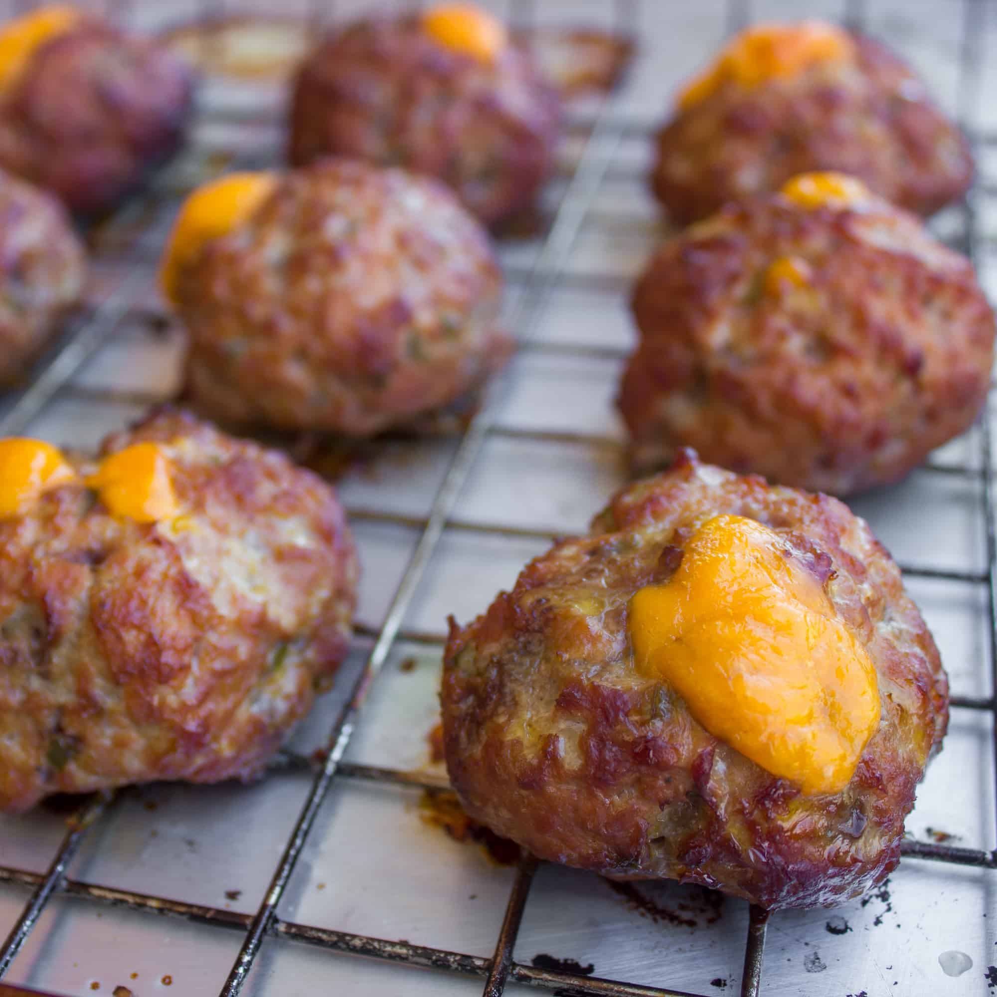 These pork meatballs are stuffed with cheddar cheese and jalapeno peppers and smoked in a Bradley smoker. Delicious, cheesy and a little spicy too!