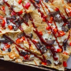 Nachos made with smoked brisket, provolone cheese, onions, peppers baked on tortilla chips with BBQ sauce. Simple party food that is smokey and delicious!