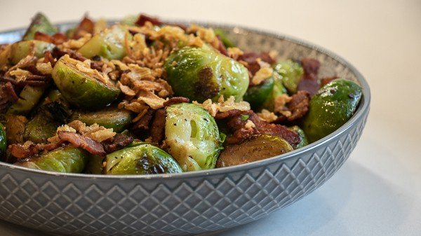 Pan seared brussels sprouts with crumbled bacon and crispy fried onions. A delicious side dish with browned caramelized brussels sprouts that taste similar to being roasted.