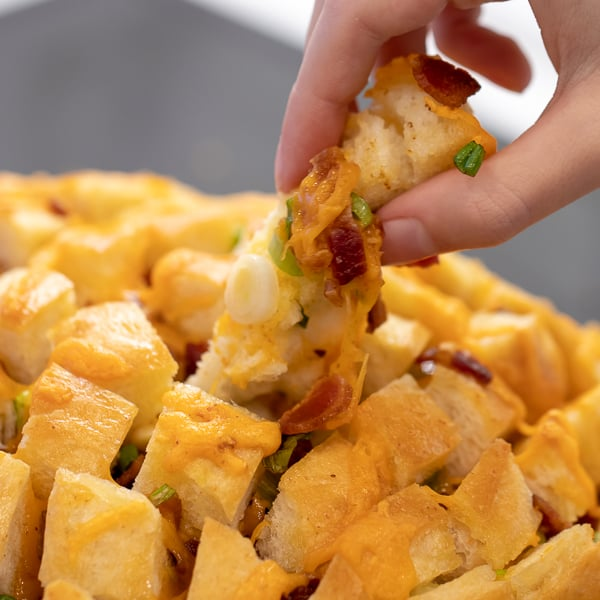 Cheesy pull apart bread made with an artisan rustic round bread loaf, sliced and filled with grated cheddar cheese, crumbled bacon and sliced green onions. Baked until cheese is bubbly!
