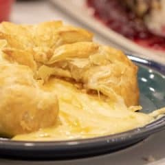 Delicious appetizer recipe of baked brie cheese wrapped in puff pastry with apricot jam and walnuts.