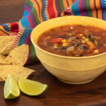 Easy to make recipe for soup full of Mexican inspired flavours. Ground beef, tomatoes, black beans, corn chili powder and more.