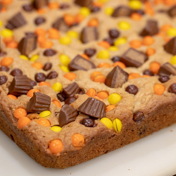 This chewy peanut butter blondie has mini Reese' Pieces, chopped peanut butter cup minis and chocolate chips. A delicious dessert and alternative to a brownie.