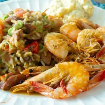 A plate of cooked shrimp with a rice and bean side dish.