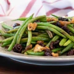 Easy side dish recipe fo fresh sautéed green beans with walnuts, dried cherries, lemon zest and lemon juice.