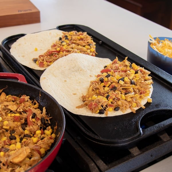 Easy recipe for Mexican quesadilla made with chicken, black beans, corn, cheddar cheese and Monterey jack. Folded and cooked on a skillet or griddle.