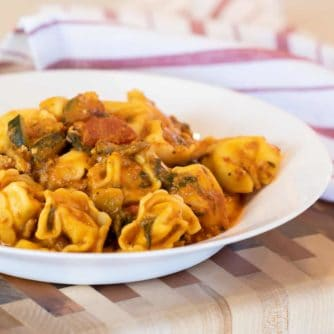 Easy pasta recipe with cheese filled tortellini, ground turkey, zucchini and spinach in a creamy tomato marinara sauce.