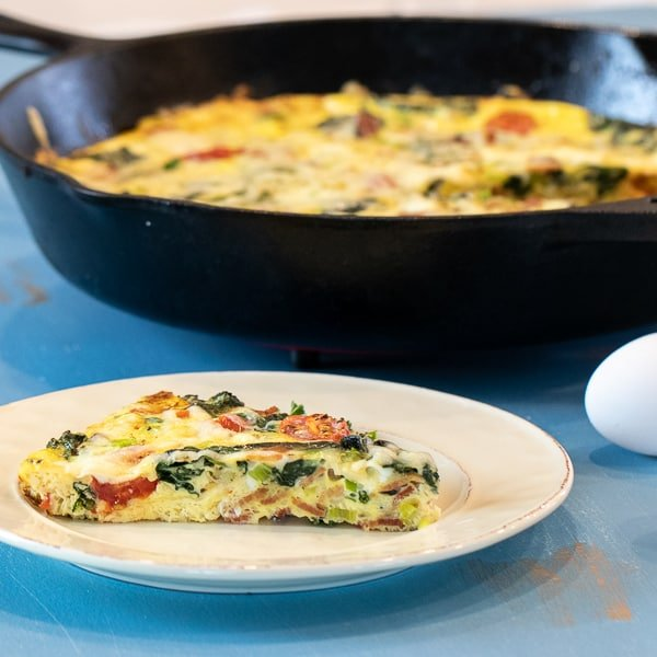 Simple recipe for an easy frittata. Baked scrambled eggs in a cast iron skillet with bacon, spinach, swiss cheese, grape tomatoes, green onions and cream.